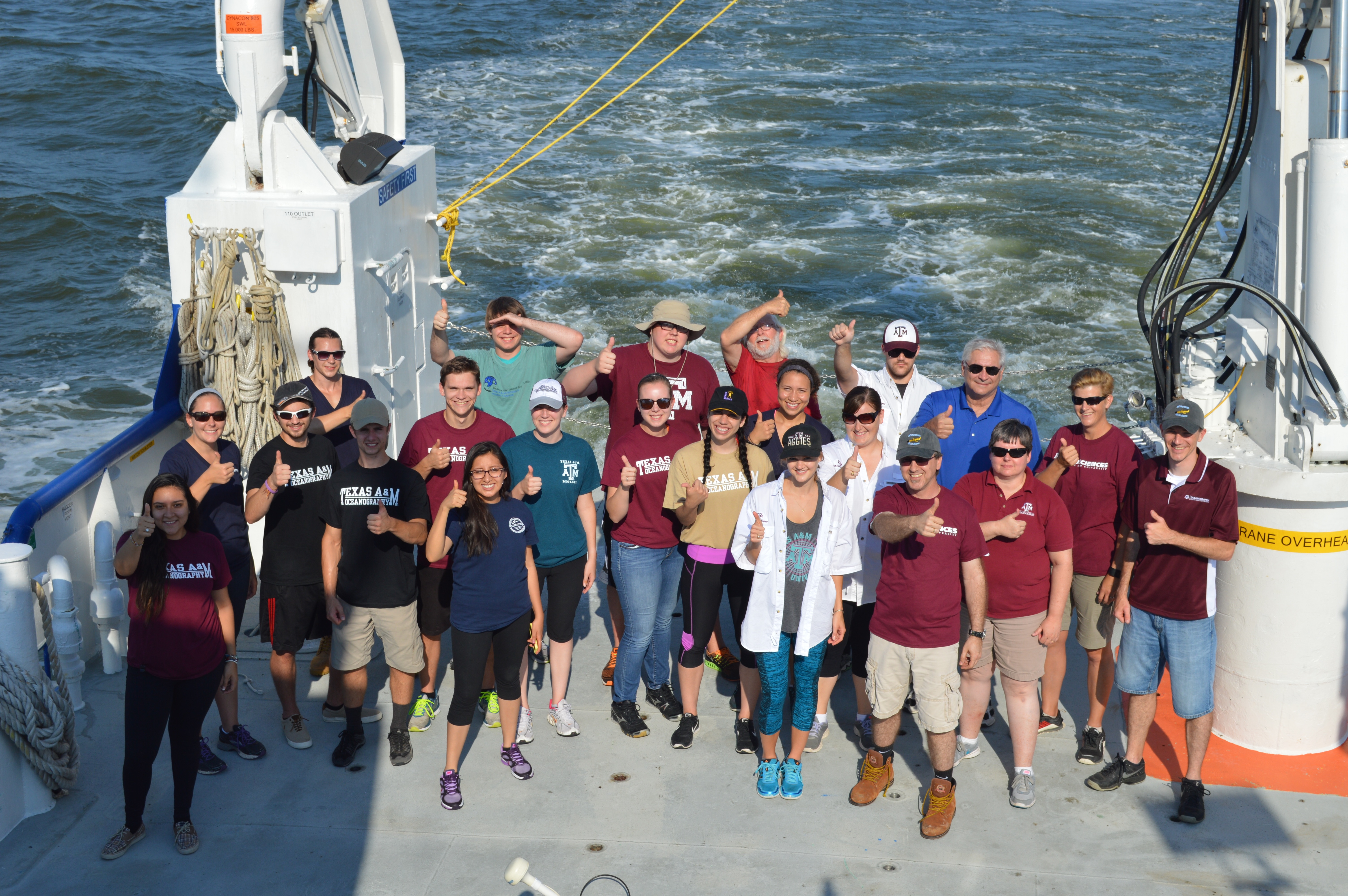 REU students on a cruise holding the Department of Oceanography flag